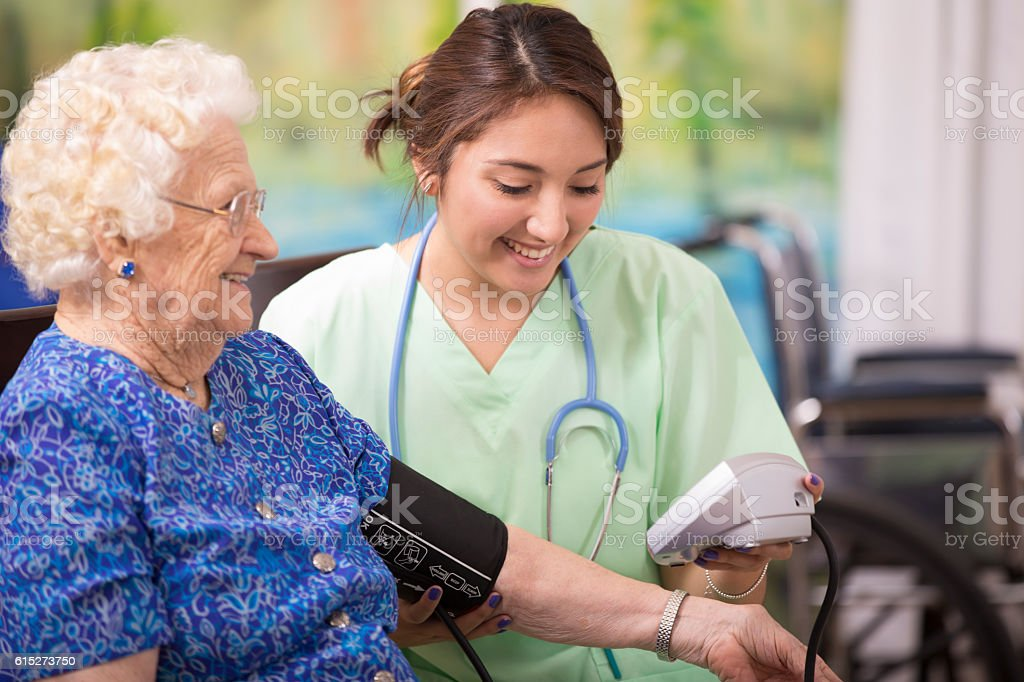 Home healthcare nurse checks blood pressure of elderly woman. stock photo