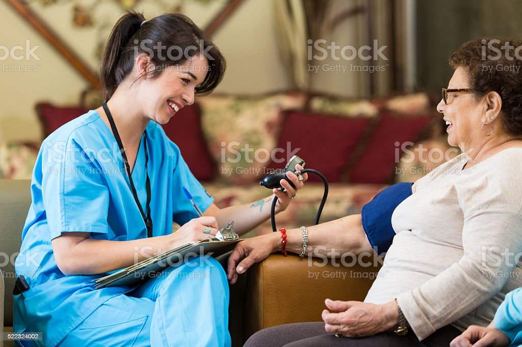 Home healthcare nurse checks patient's blood pressure stock photo