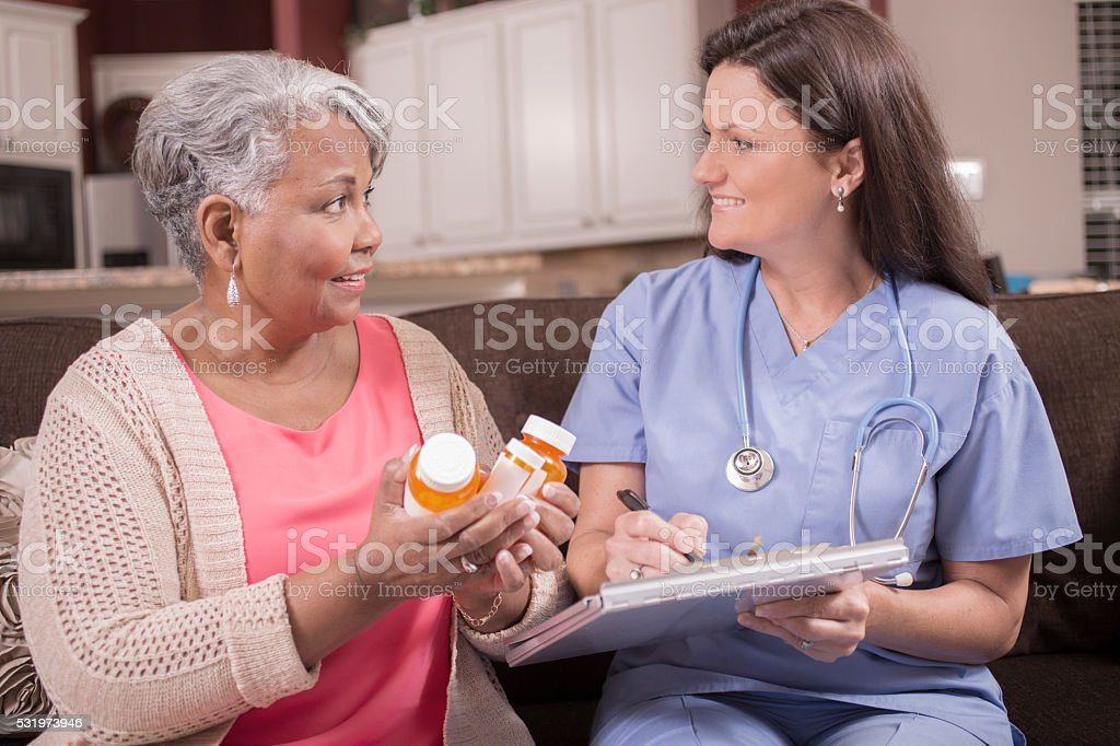 Home healthcare nurse discussing medications to senior adult woman. stock photo