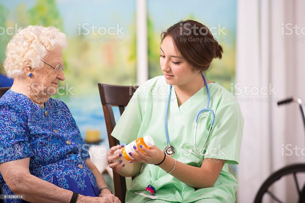 Home healthcare nurse explains prescription medicine to elderly woman. stock photo