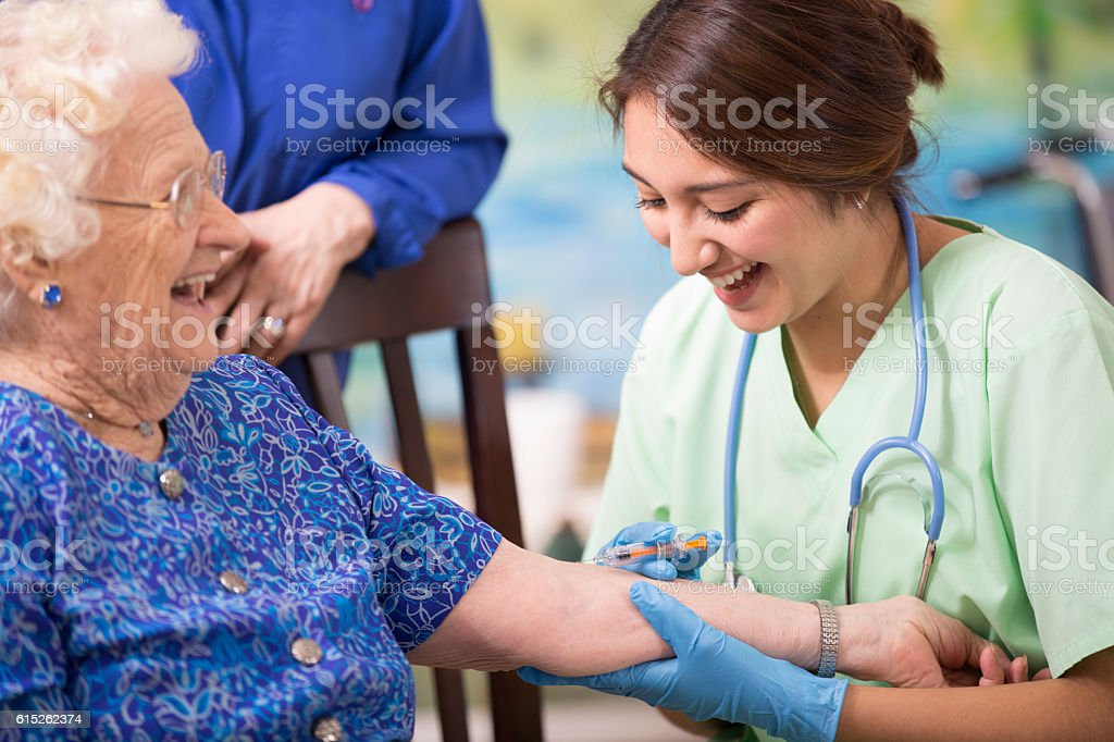 Home healthcare nurse giving injection to elderly woman. stock photo