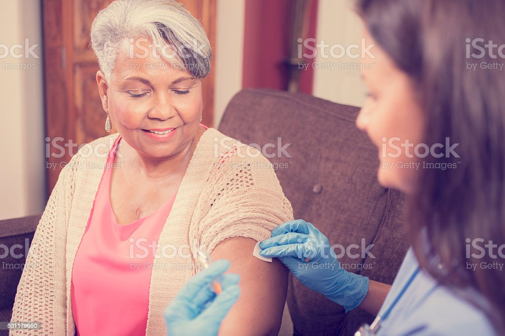 Home healthcare nurse giving injection to senior adult woman. stock photo