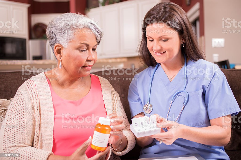 Home healthcare nurse giving medications to senior adult woman. stock photo