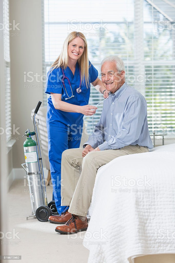 Home healthcare nurse helping elderly man with oxygen stock photo