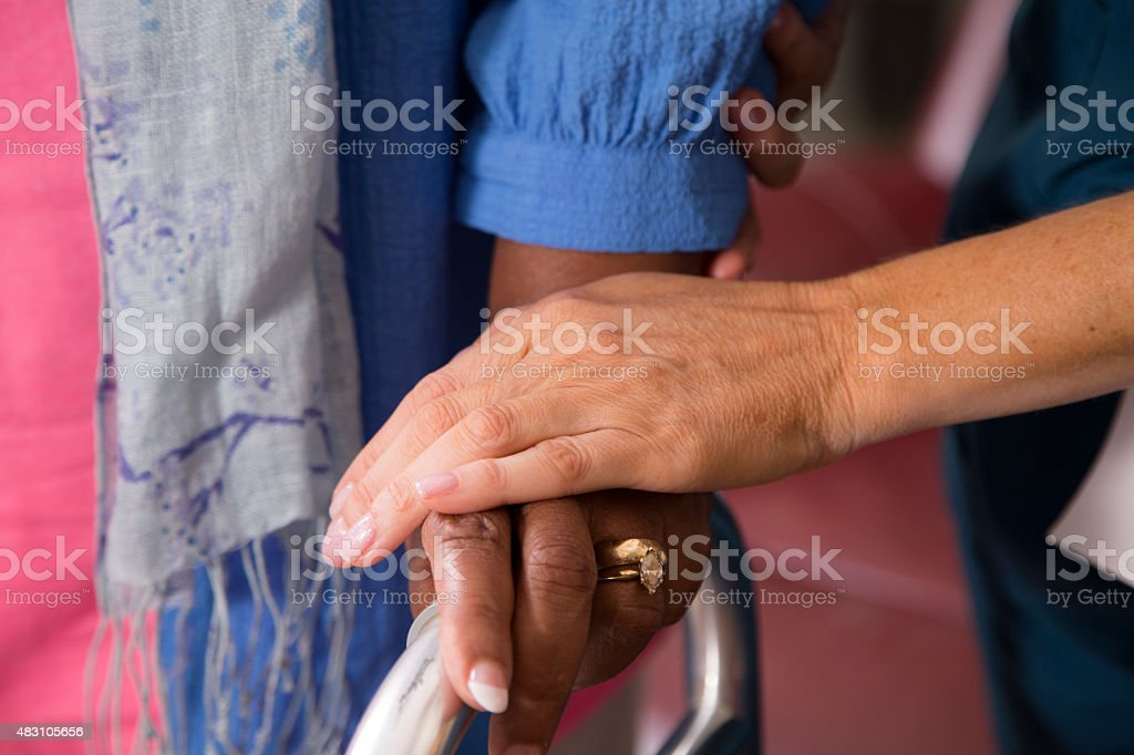 Home healthcare nurse helps senior woman use walker. stock photo