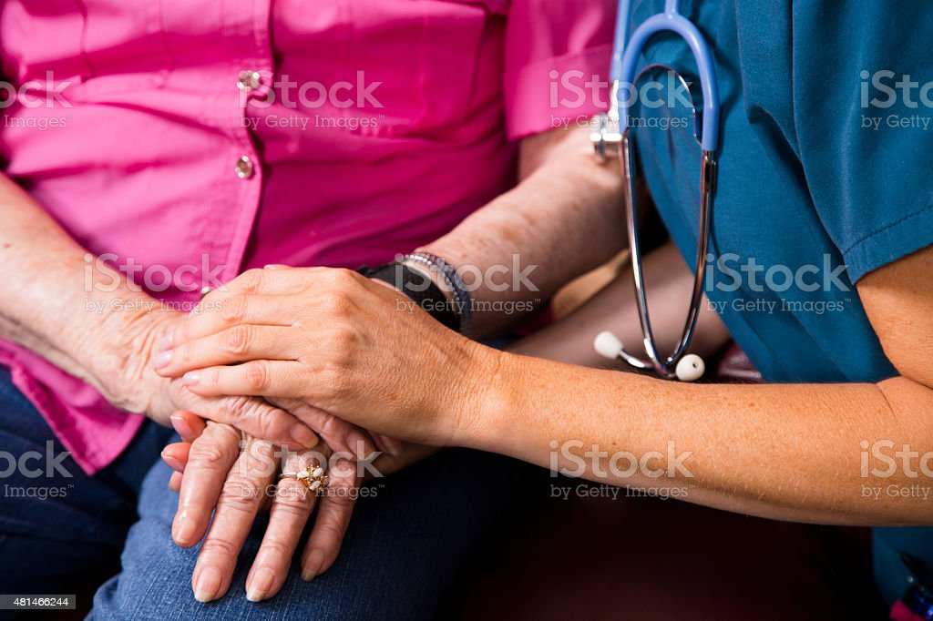 Home healthcare nurse holds senior woman's hands. Consoling. Kindness. stock photo
