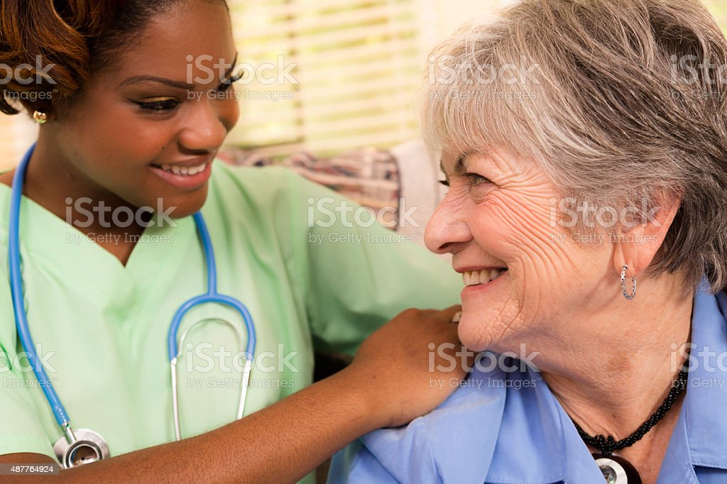 Home healthcare nurse or doctor with senior adult patient. Home. stock photo
