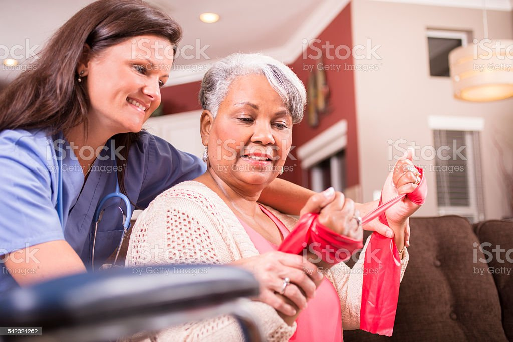 Home healthcare nurse, physical therapy with senior adult woman. stock photo