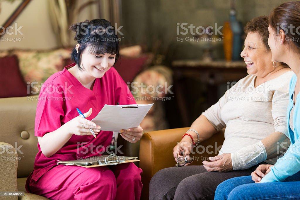 Home healthcare nurse reviews patient information stock photo