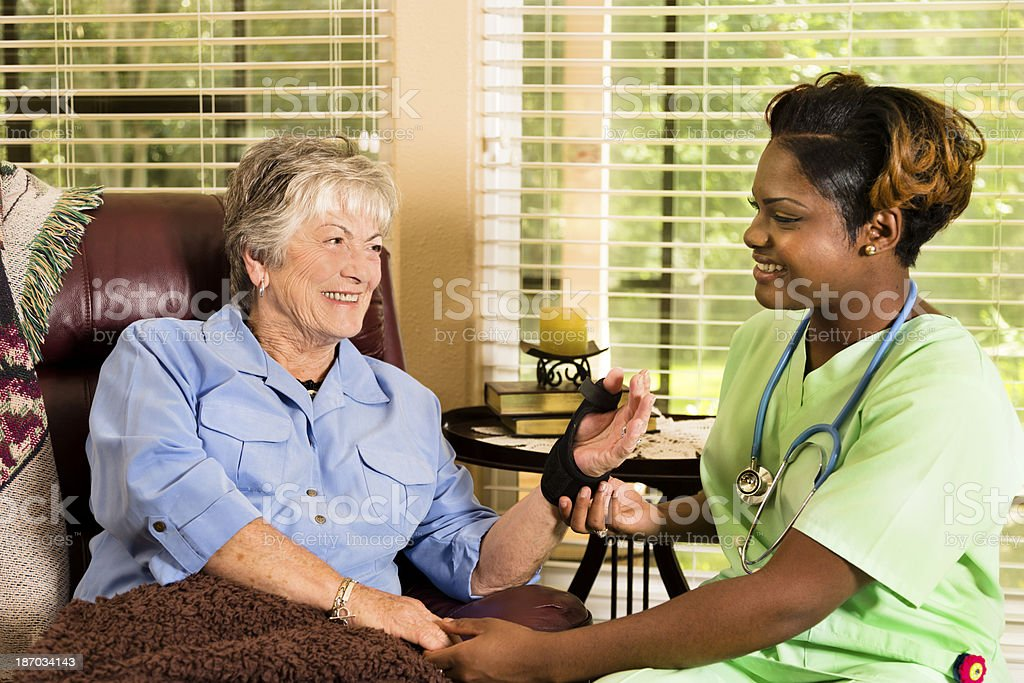 Home healthcare nurse visiting injured patient stock photo