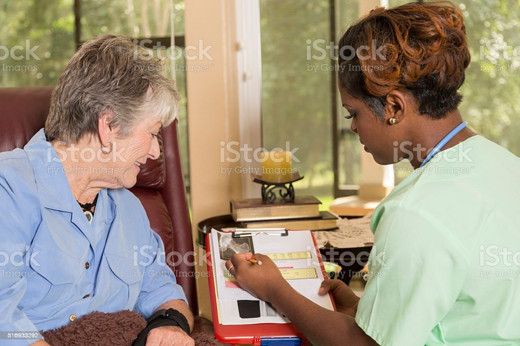 Home healthcare nurse with senior adult patient. Consulation. Medical results. stock photo