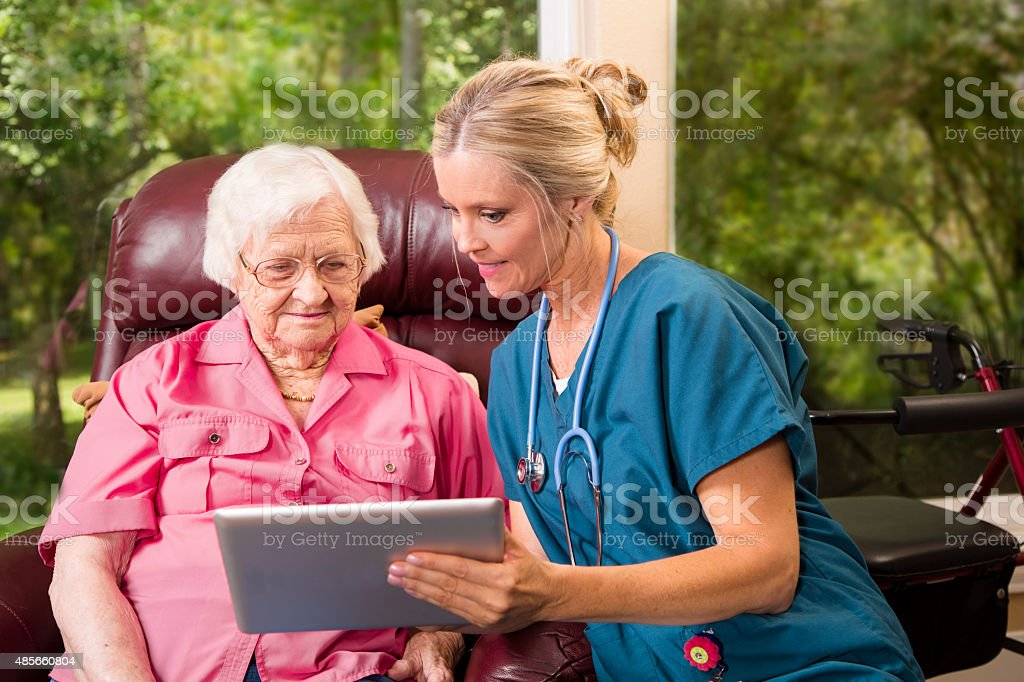 Home healthcare nurse with senior adult patient. Digital tablet. stock photo
