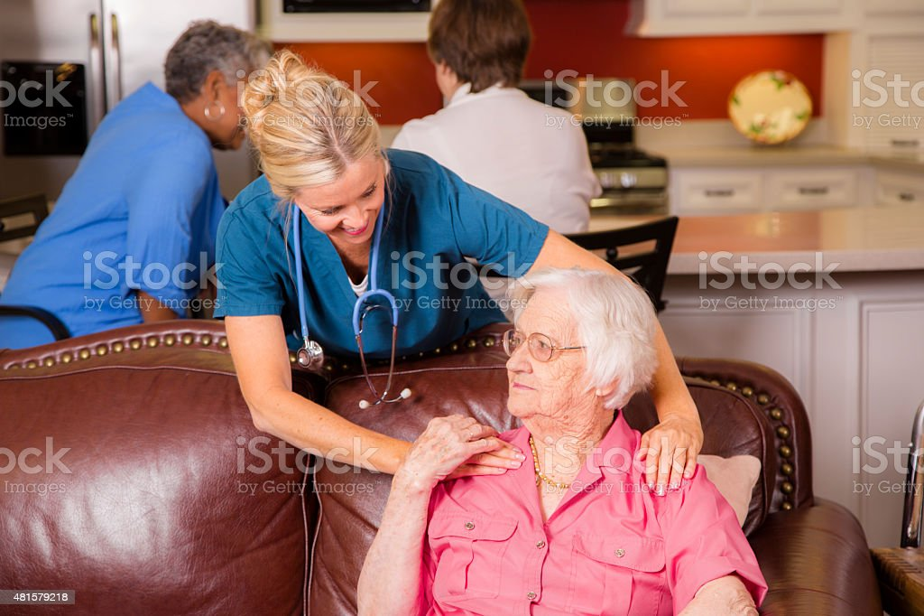 Home healthcare nurse with senior adult patient. House call. stock photo