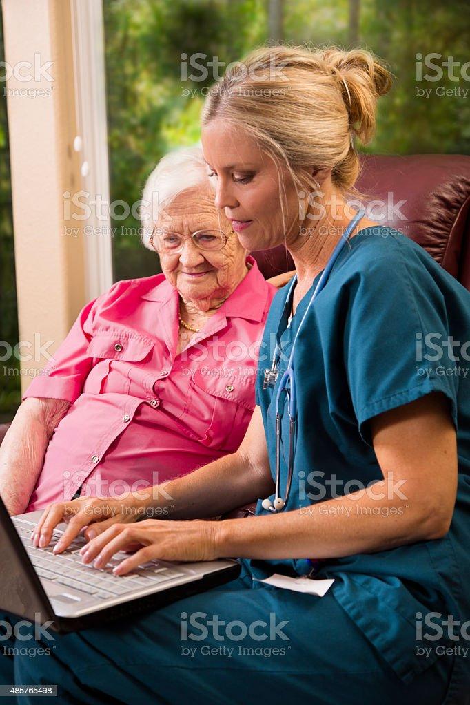 Home healthcare nurse with senior adult patient. Laptop. stock photo