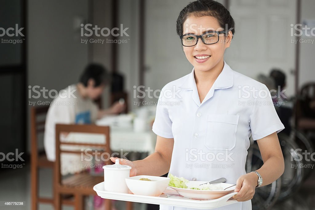 Home healthcare nurse with senior adult patient. Meal delivery stock photo