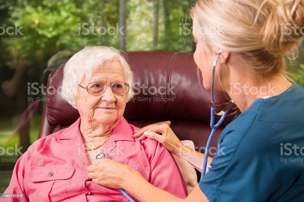 Home healthcare nurse with senior adult patient. Medical exam. stock photo