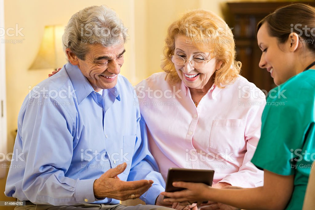 Home healthcare nurse with senior couple stock photo