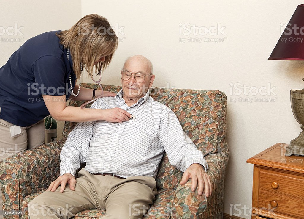 Home Healthcare Worker Checking Heart of Senior Patient stock photo
