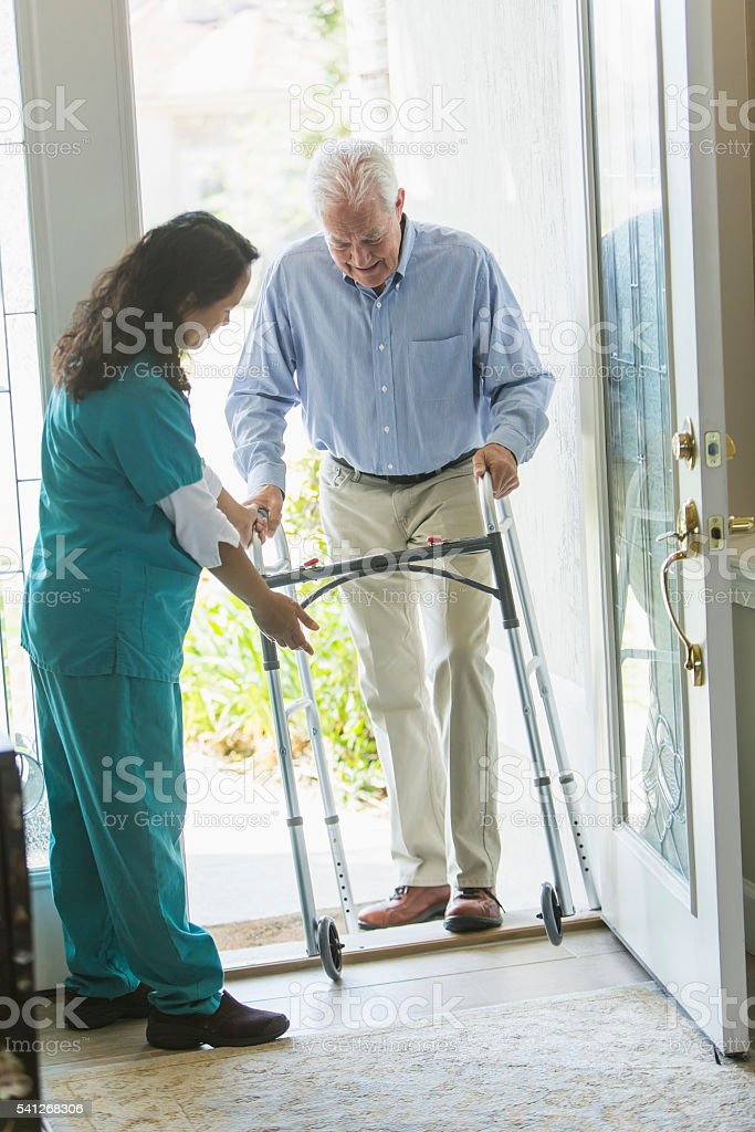 Home healthcare worker helping elderly man with walker stock photo