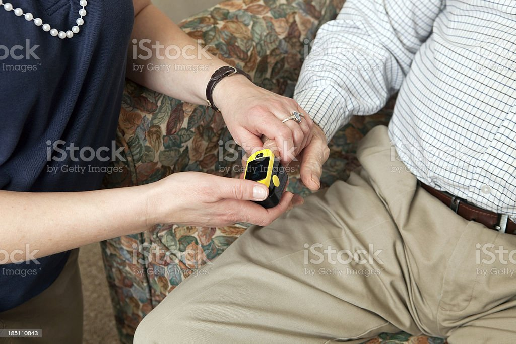Home Healthcare Worker Using Pulse Oximeter on Senior Patient stock photo