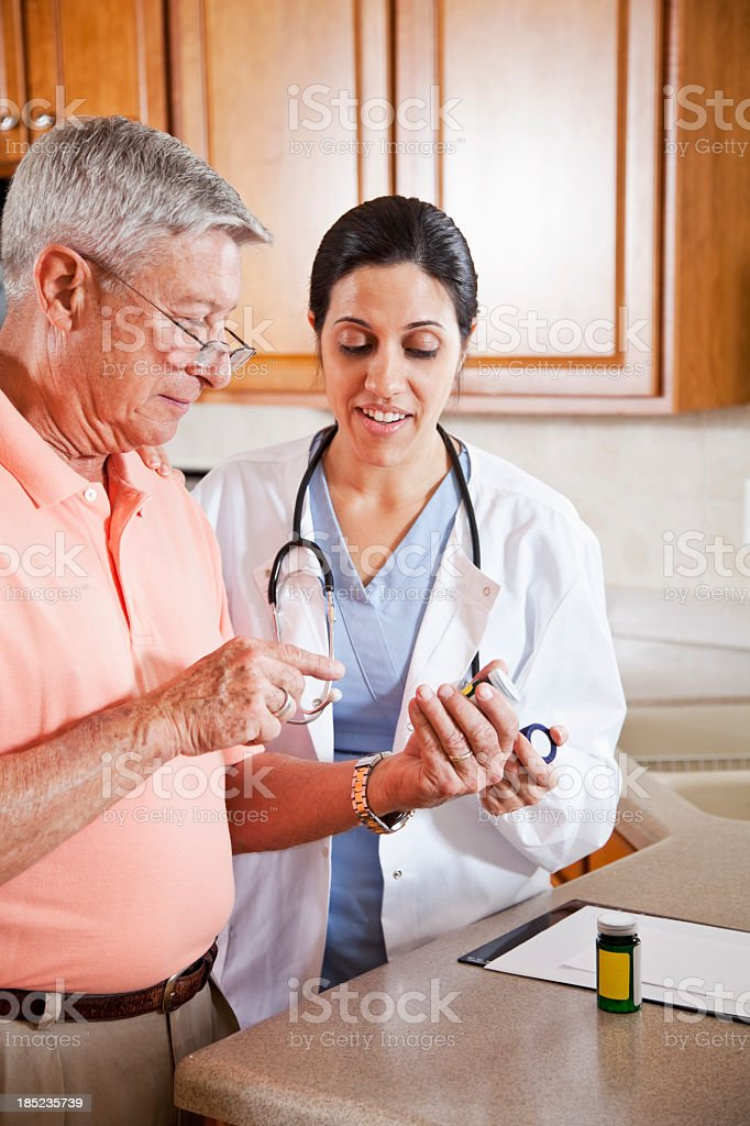 Home healthcare worker with prescriptions for senior man stock photo