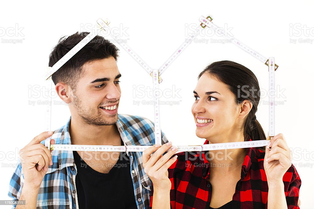 Home improvement - Couple holding a house shaped measure royalty-free stock photo