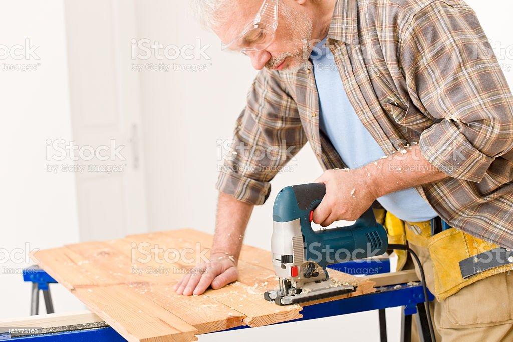 Home improvement - handyman cut wood with jigsaw royalty-free stock photo