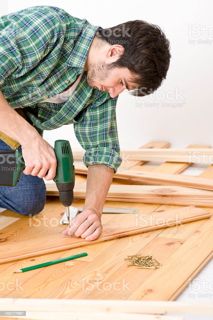 Home improvement - handyman installing wooden floor royalty-free stock photo
