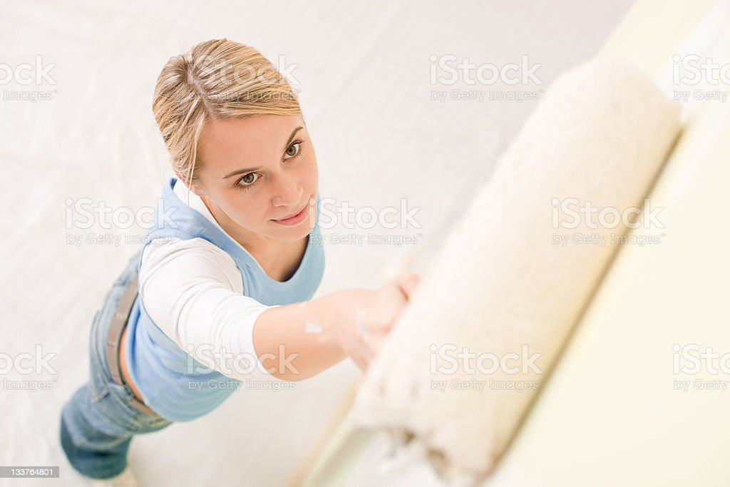 Home improvement - handywoman painting wall royalty-free stock photo