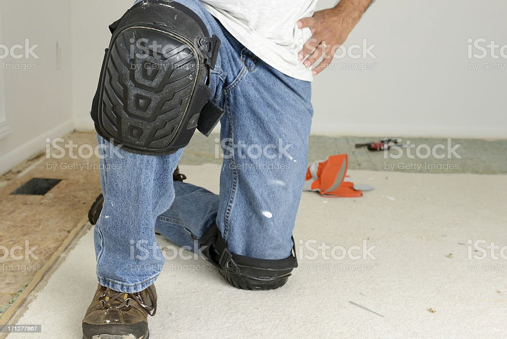 Home Improvement: Kneeling Worker's Legs With Kneepads stock photo