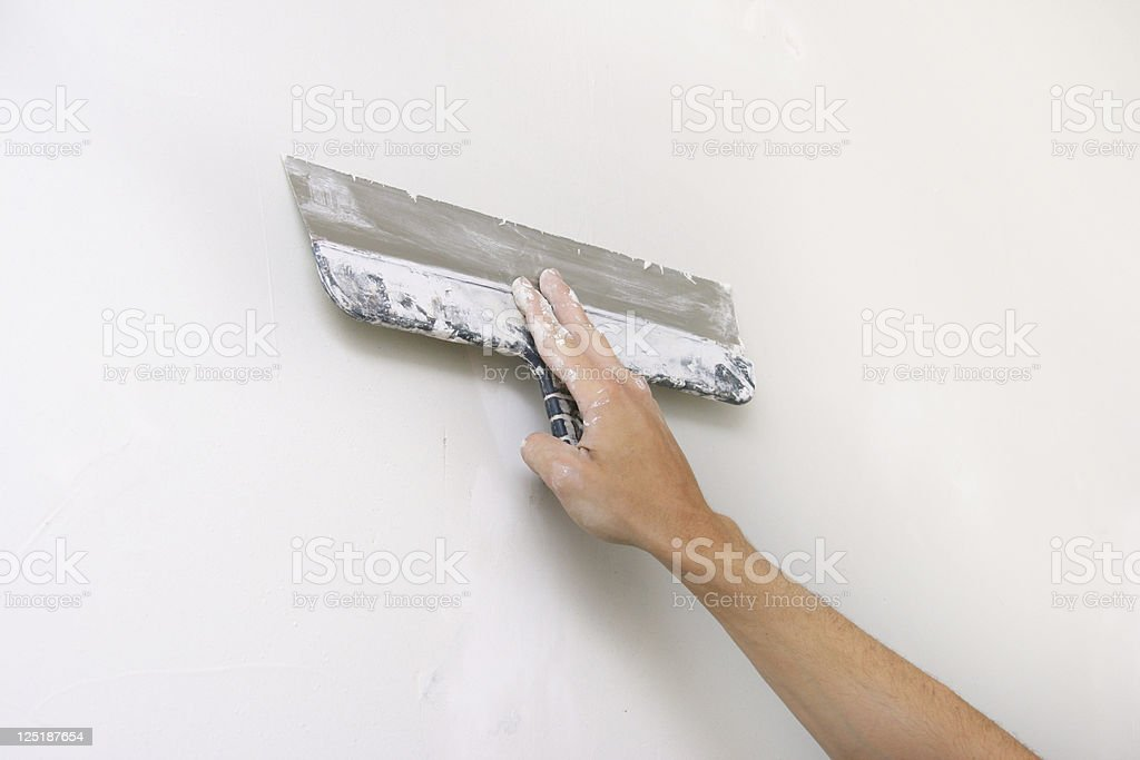 home improvement - putty knife in hand royalty-free stock photo