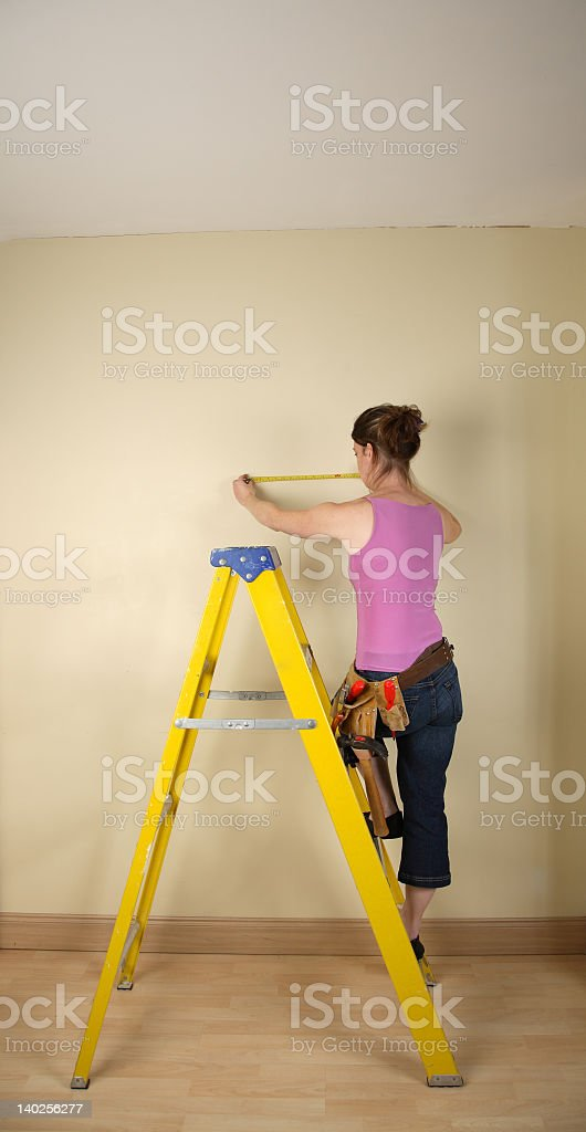 Home improvement with woman on ladder royalty-free stock photo