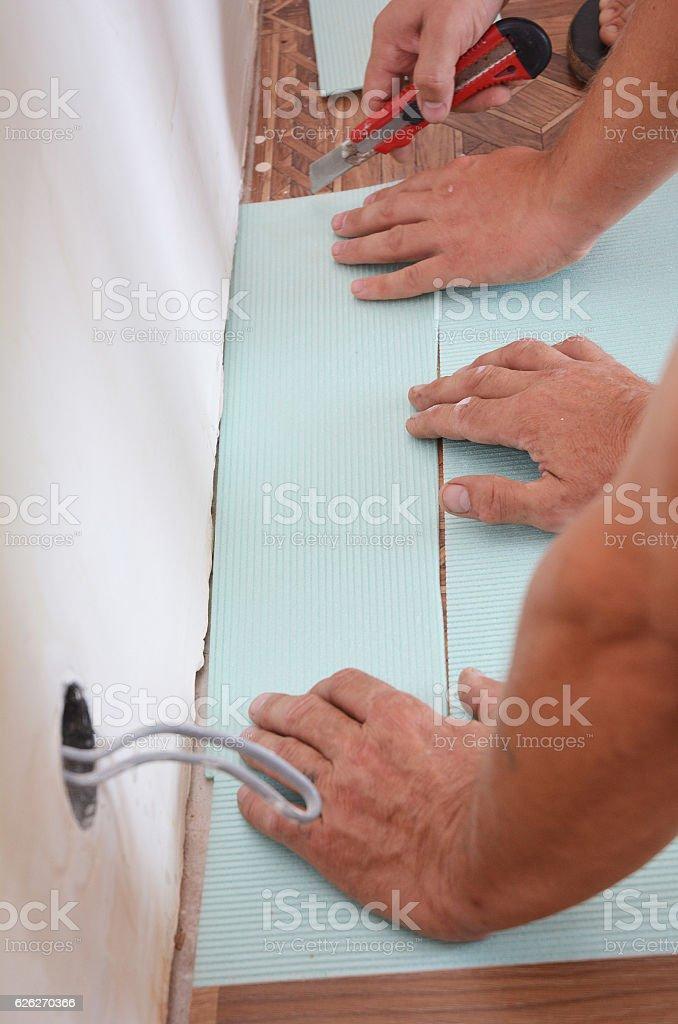 Home improvement - workers installing laminate flooring. stock photo
