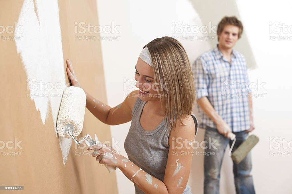 Home improvement: Young man and woman painting wall royalty-free stock photo
