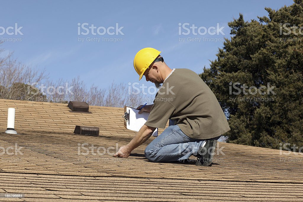 Home inspector checking the roof of a house. stock photo