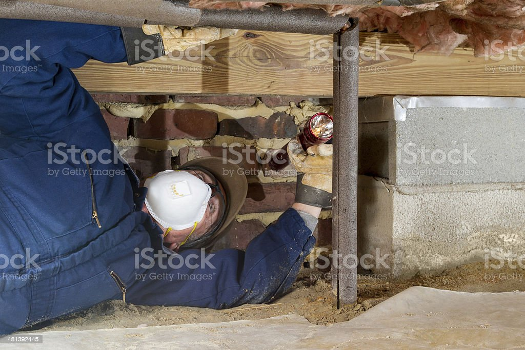 Home inspector examines a freeze protected crawl space water line. stock photo