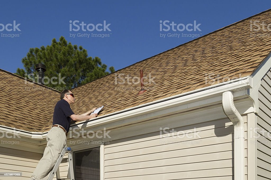 Home inspector examines a residential roof vent pipe. stock photo
