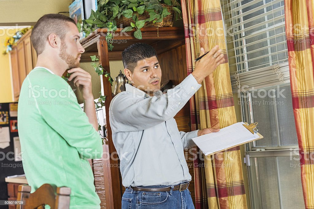 Home inspector explaining damage and repairs to homeowner stock photo
