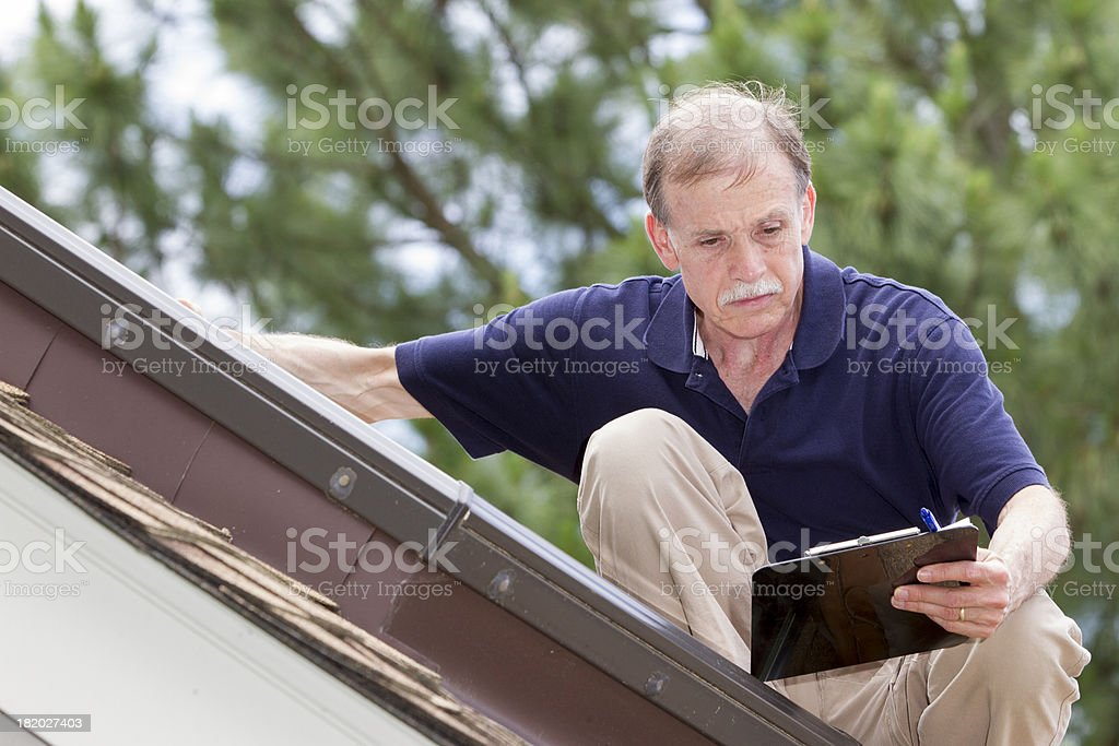 Home inspector on a roof examins a residential skylight. royalty-free stock photo