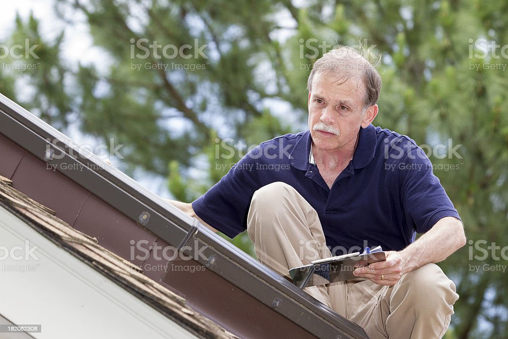 Home inspector on a steep roof examins a residential skylight. royalty-free stock photo