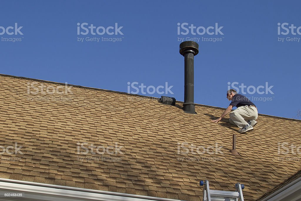 Home Inspector, on the roof, examines a roof gas vent. stock photo