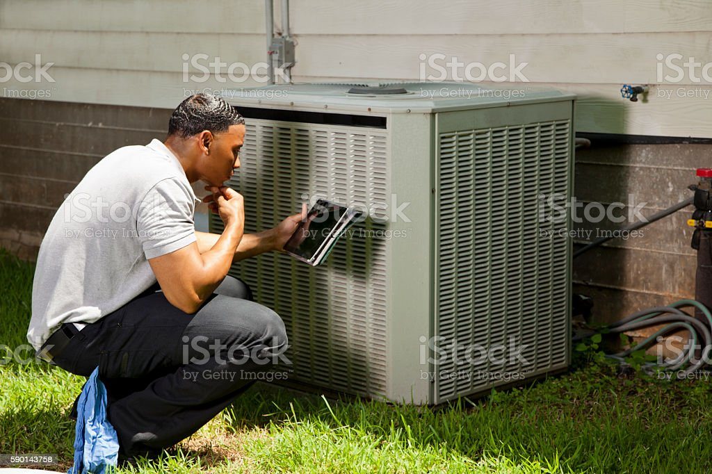 Home inspector, repairman uses digital tablet to check air conditioners. stock photo