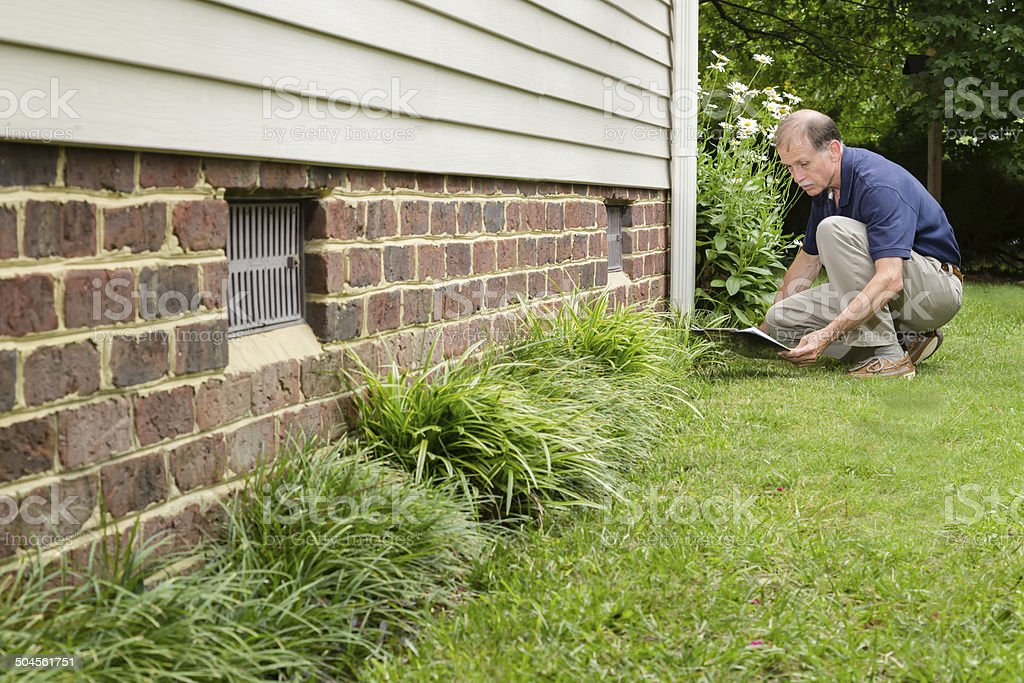 Home inspector with clipboard examines a home's brick foundation stock photo