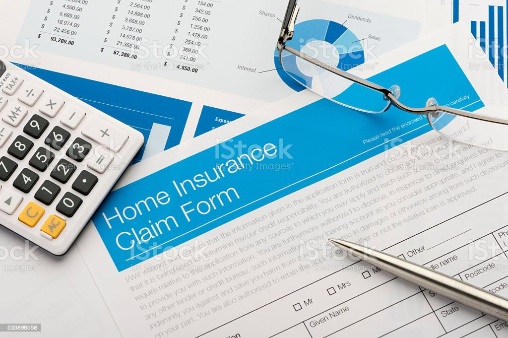Home insurance claim form on a desk with paperwork. There is also a...