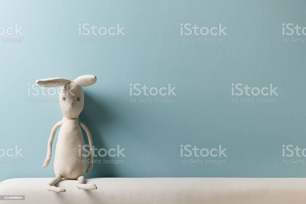 Home interior. Childhood. Blue background. Toy sitting on a couch. stock photo