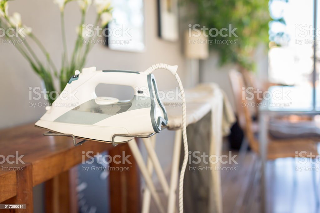 Home interior with iron and ironing board stock photo