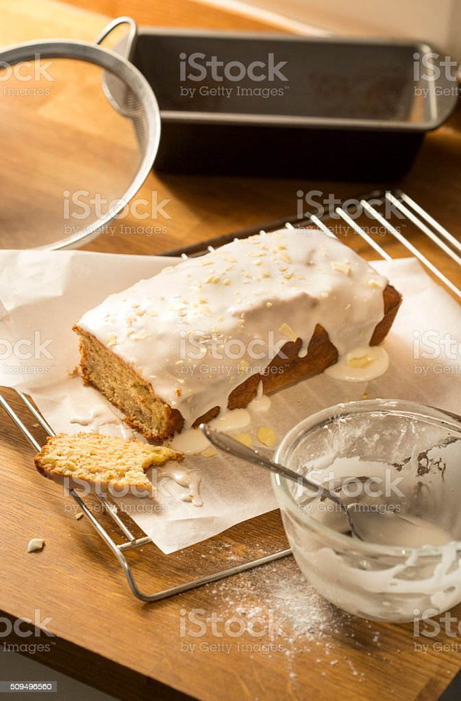 Home made loaf cake with runny icing on wooden table stock photo