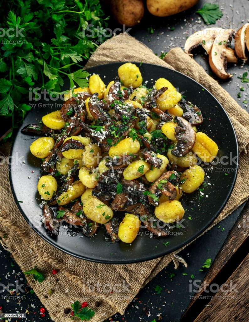 Home made potato gnocchi with mushrooms, chopped parsley and parmesan cheese stock photo