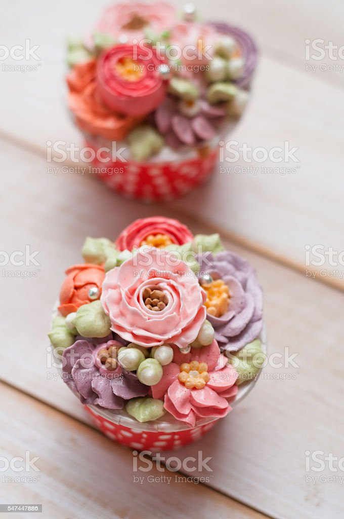 home made sponge cupcakes with flowers buttercream stock photo