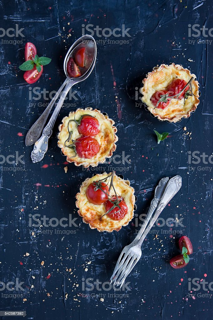 home made tartlets with cherry tomatoes on black stock photo